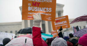 Demonstrators in support of U.S. President Barack Obama's health-care law contraception requirement hold up signs outside the U.S. Supreme Court on Tuesday. Hobby Lobby is seeking a religious exemption from the requirement that employers cover some forms of birth control as part of worker-insurance plans. Photographer: Andrew Harrer/Bloomberg