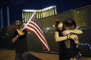 In this Oct. 1, 2018, file photo, Megan Murphy, right in hat, embraces Cara Knoedler as Kenneth Wright wipes his eyes on the first anniversary of the mass shooting in Las Vegas. In the two years since the deadliest mass shooting in modern U.S. history, the federal government and states have taken some action to tighten gun regulations. But advocates say they're frustrated more hasn't been done since the attack in Las Vegas killed 58 people on Oct. 1, 2017, and that mass shootings keep happening across the country. AP Photo by John Locher,