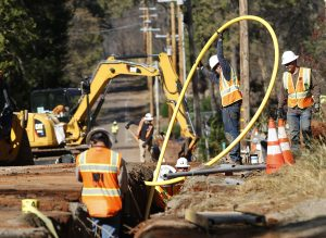 In this Oct. 18, 2019, file photo, Pacific Gas and Electric Company workmen bury utility lines in Paradise, Calif. California says sparks from power lines and other electrical equipment caused many of the state's major wildfires in 2017 and 2018. Federal officials have awarded $176 million over several years to help states and territories bury power lines. AP Photo by Rich Pedroncelli