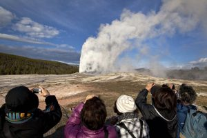 In this May 2011 file photo, tourists photograph Old Faithful erupting in Yellowstone National Park, Wyo. On Tuesday, the National Park Service announced that Yellowstone and Grand Teton National Parks would be closed until further notice, and no visitor access will be permitted to either park. AP Photo by Julie Jacobson
