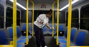 Stacy Loggins, a janitorial supervisor for Metro, wipes down the interior of a bus with disinfectant Thursday at a Metro facility in St. Louis. States across the U.S. are allocating hundreds of millions of dollars to respond to the coronavirus, even as the U.S. government prepares to send billions more their way. Photo by Christian Gooden of the St. Louis Post-Dispatch via AP