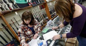 Andrea Schry, right, fills out the buyer part of legal forms to buy a handgun as shop worker Missy Morosky fills out the vendors parts after Dukes Sport Shop reopened, Wednesday in New Castle, Pa. under the new conditions specified for gun stores. The store had closed last week when Pennsylvania Gov. Tom Wolf ordered a shutdown of non-essential businesses to slow the spread of the coronavirus. AP Photo by Keith Srakocic