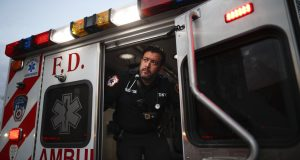 """FDNY paramedic Alex Tull, who has recently recovered from COVID-19, prepares to begin his shift outside EMS station 26, the """"Tinhouse,"""" in the Bronx borough of New York. AP Photo by John Minchillo"""
